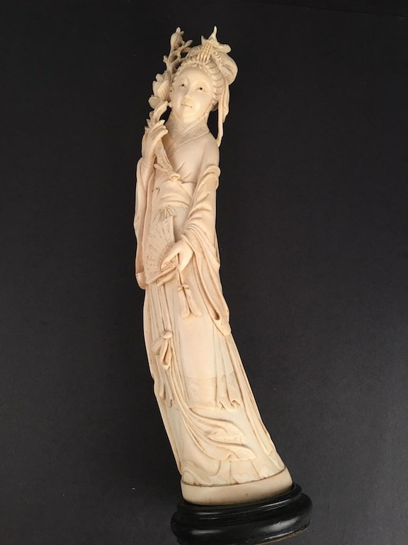 Antique carved standing beauty holding a fan and a