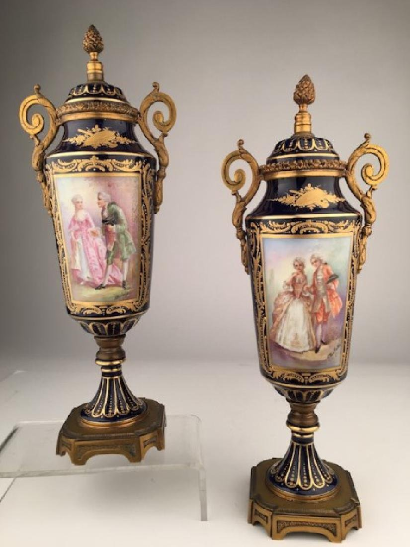 Pair of Sevres urns with gold dore bronze handles and