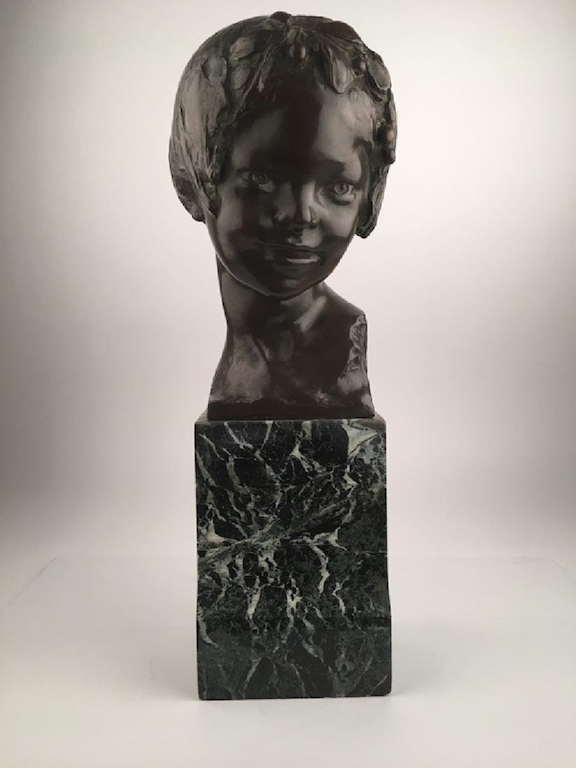 Bronze bust of a young girls head mounted on a black