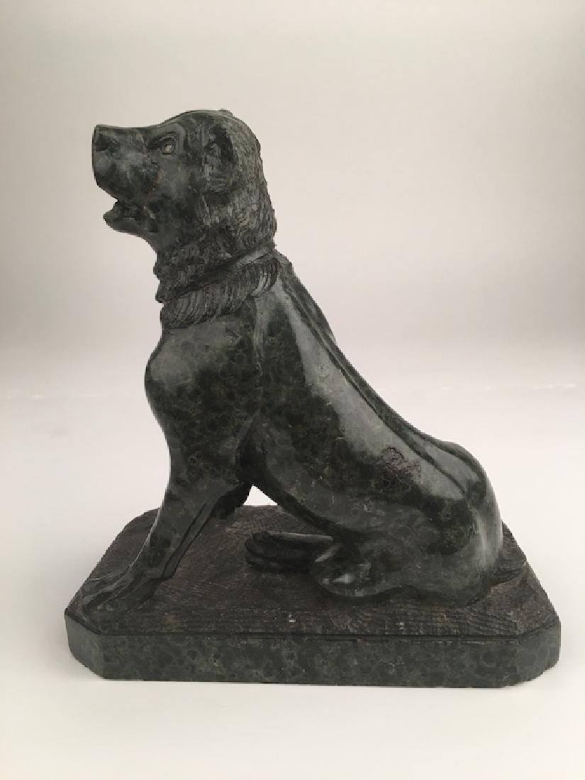 Carved green granite dog sitting on the hind legs
