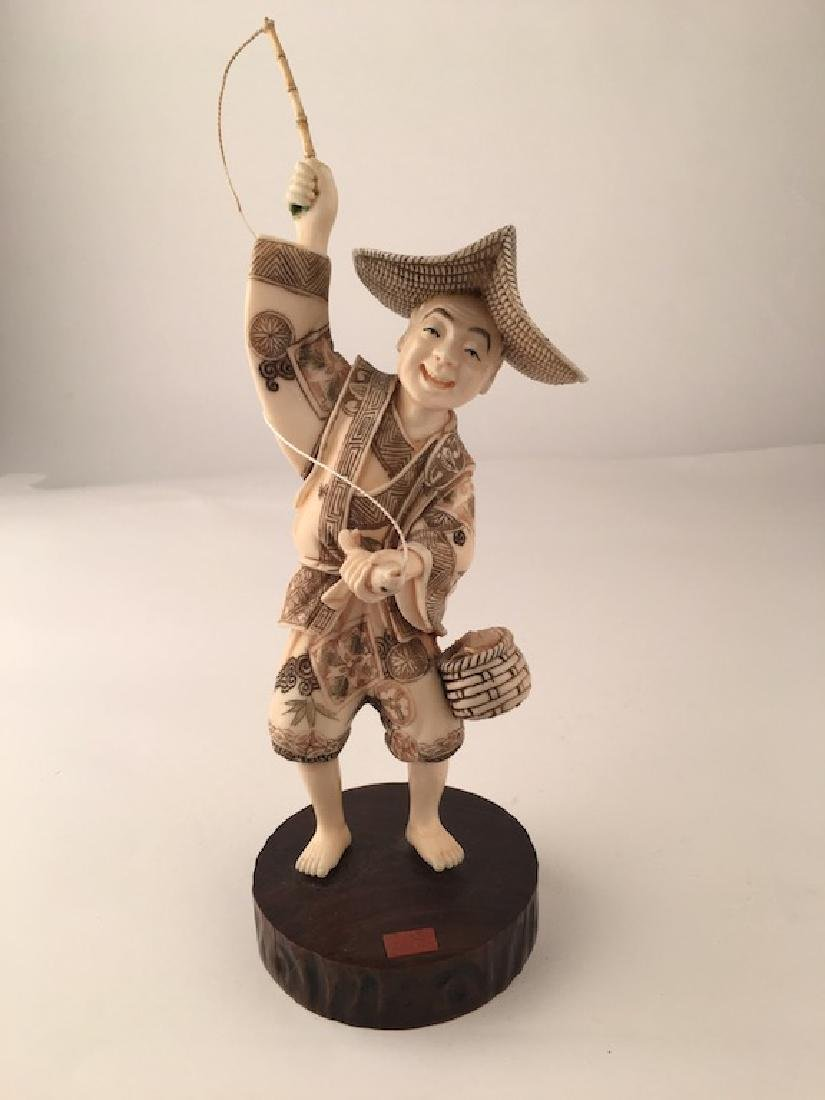 Carving of a fisherman with his fish basket to his