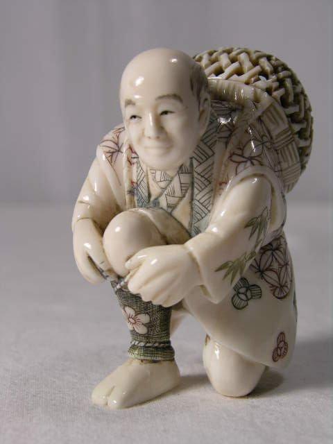 4101: IVORY FIGURE. A JAPANESE MAN KNEELING DOWN TYING