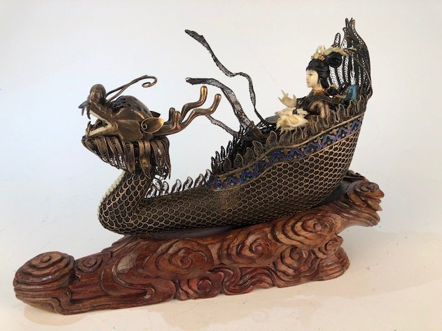 Chinese figure of a woman in a silver boat.