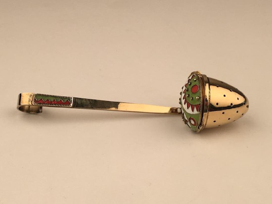 Silver gilt and enamel tea strainer.