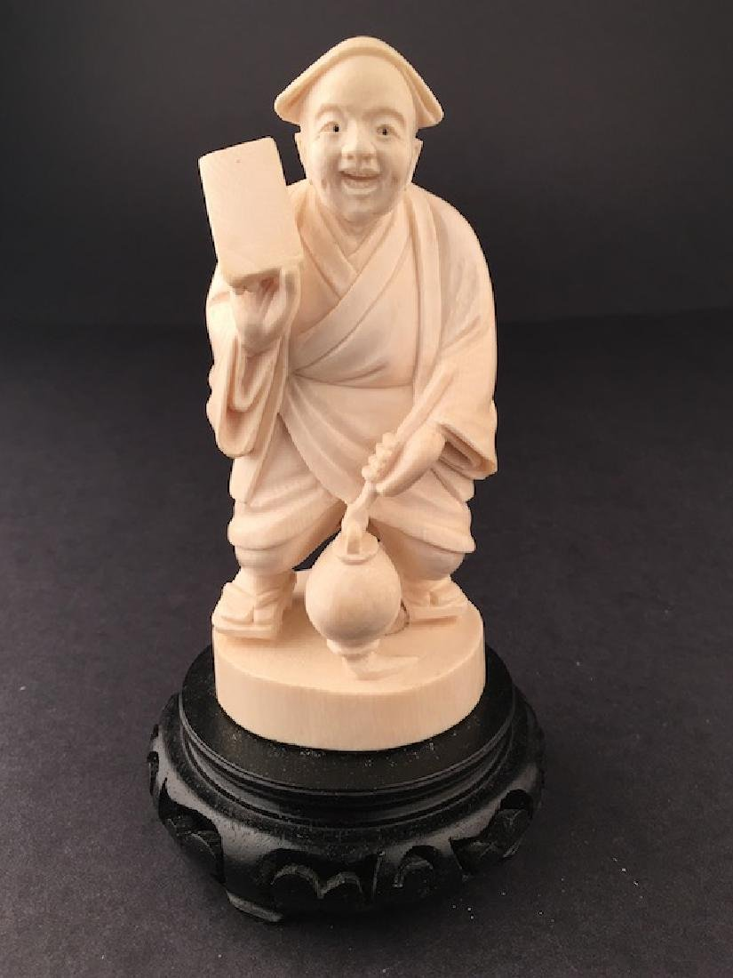 Carved figure of a man standing holding a jug and a