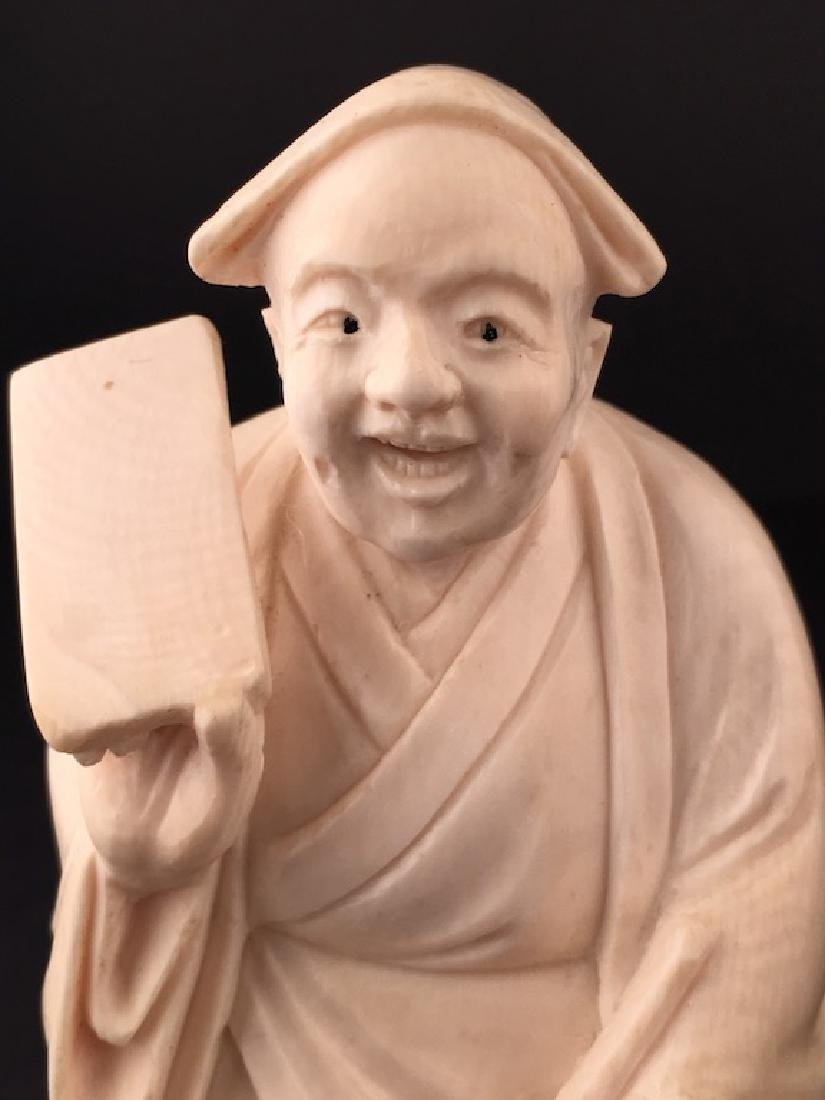 Carved figure of a man standing holding a jug and a - 2