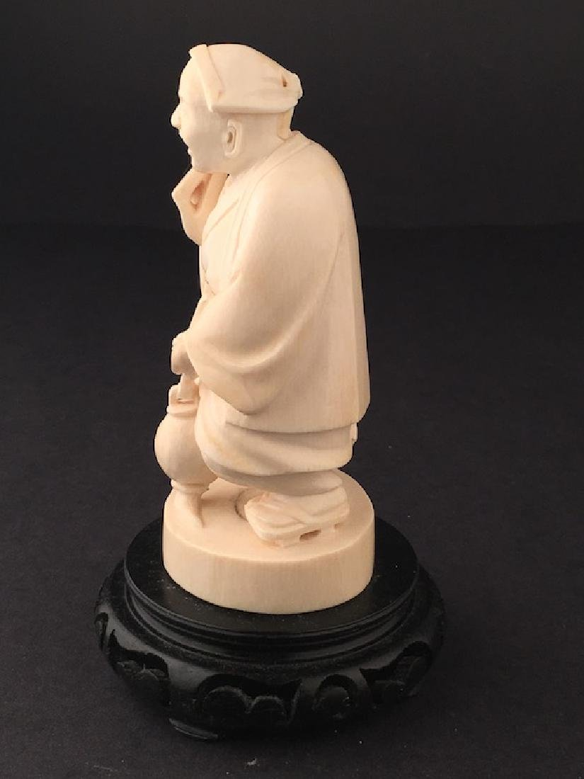 Carved figure of a man standing holding a jug and a - 3