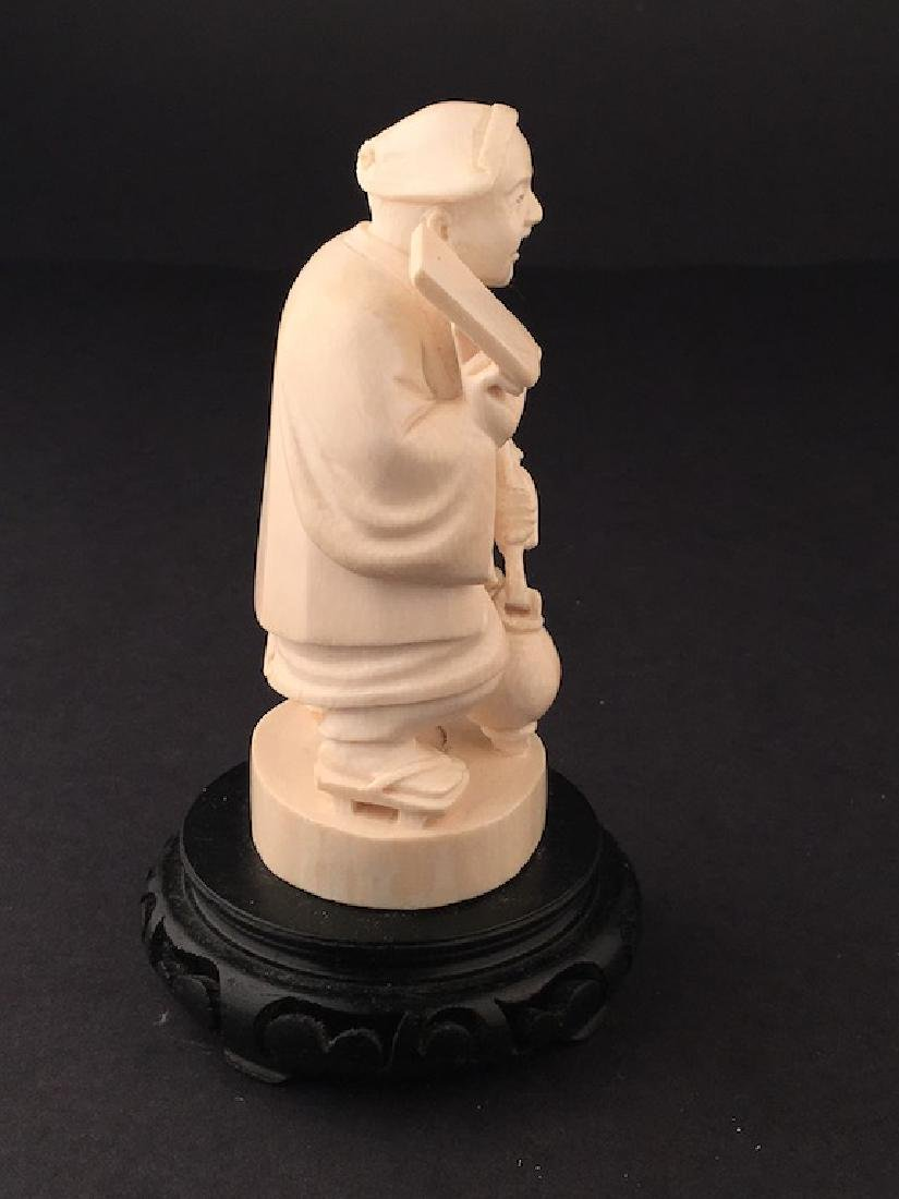 Carved figure of a man standing holding a jug and a - 5
