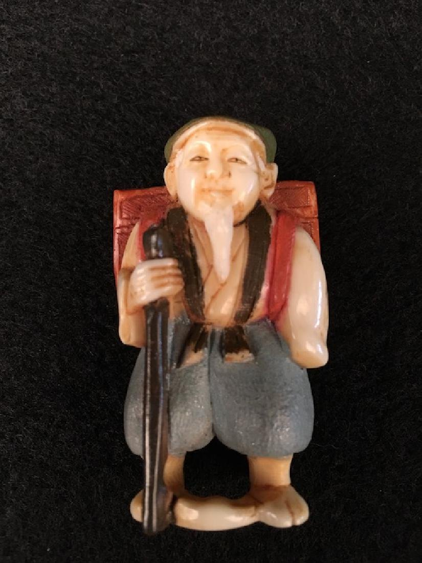Carved Netsuke figure of a man with a staff and wearing