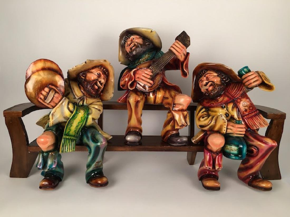 Three hand carved and painted men sitting on a wood