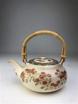 A fine porcelain teapot with its original bamboo handle