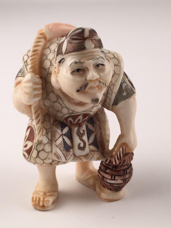 Carved Japanese Netsuke man with a fish on his back.