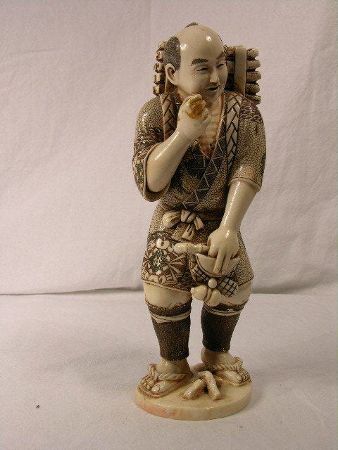 2766: IVORY CARVING OF A JAPANESE MAN CARRYING A SACK O