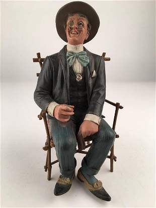 Antique terra-cotta figure of a man seated in a chair.