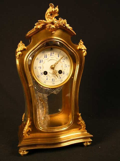 267: FRENCH MANTLE CLOCK IN A GOLD CASE WITH  BEVELED G