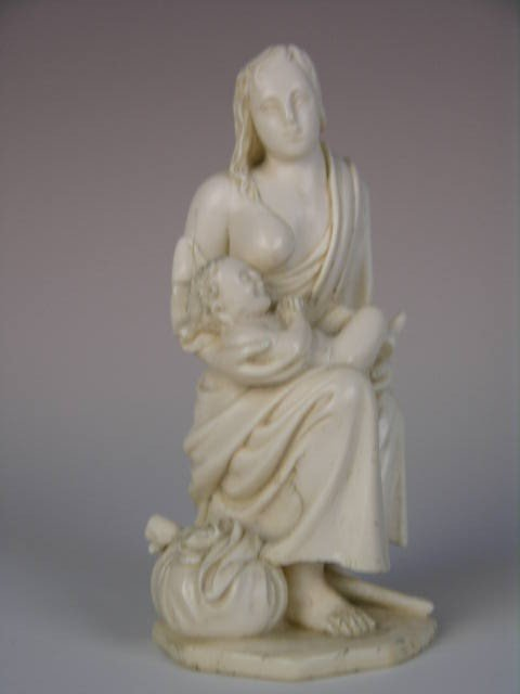 21: A CONTINENTAL CARVED IVORY FIGURINE OF A MOTHER AND