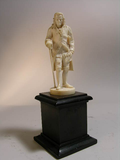 24: EUROPEAN CARVED IVORY FIGURE OF VOLTAIRE WITH A CAN