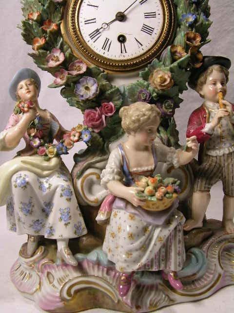 10: PORCELAIN MANTEL CLOCK WITH FOUR FIGURINES.  CHIP T