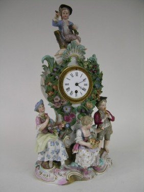 PORCELAIN MANTEL CLOCK WITH FOUR FIGURINES.  CHIP T