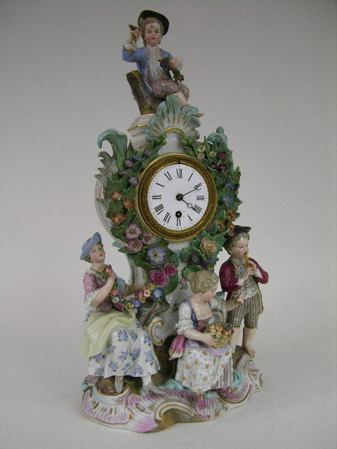 12: PORCELAIN MANTEL CLOCK WITH FOUR FIGURINES.  CHIP T