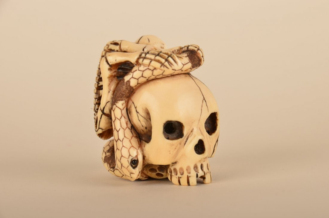 20: A good Chinese carved ivory skull with snake and sk