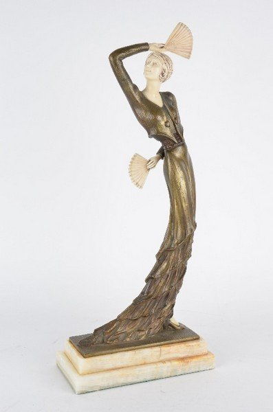 A patinated bronze female dancer in a long frilled