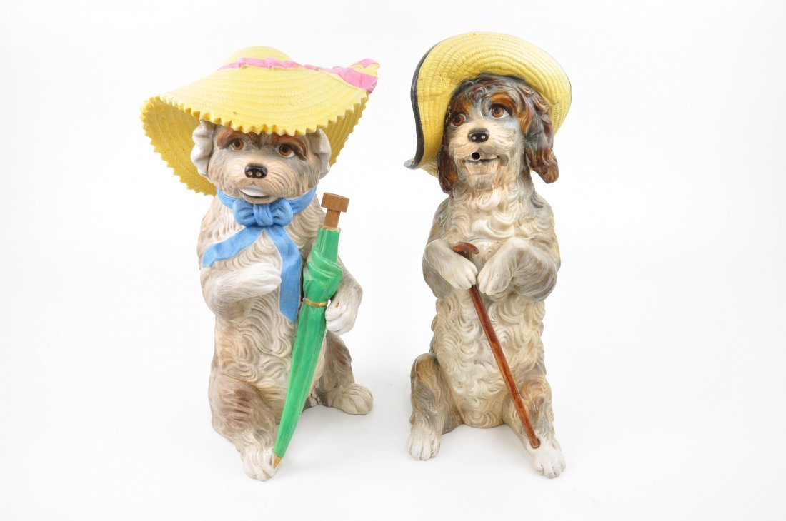 Antique pair of dogs dressed each with a hat.