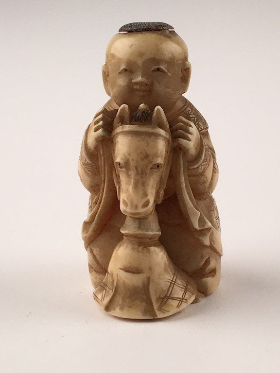 Carved Japanese Netsuke figure of a young child riding