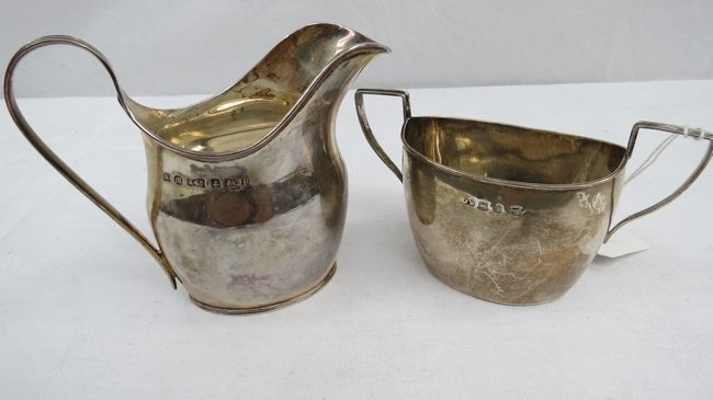 A silver milk jug of plain form with reeded lip, marked