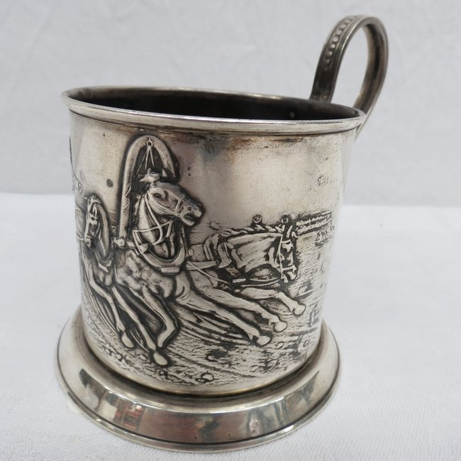 A Russian white metal cup holder with embossed troika a