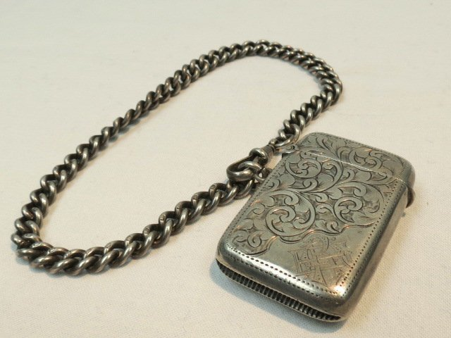 A silver vesta case on curb link chain
