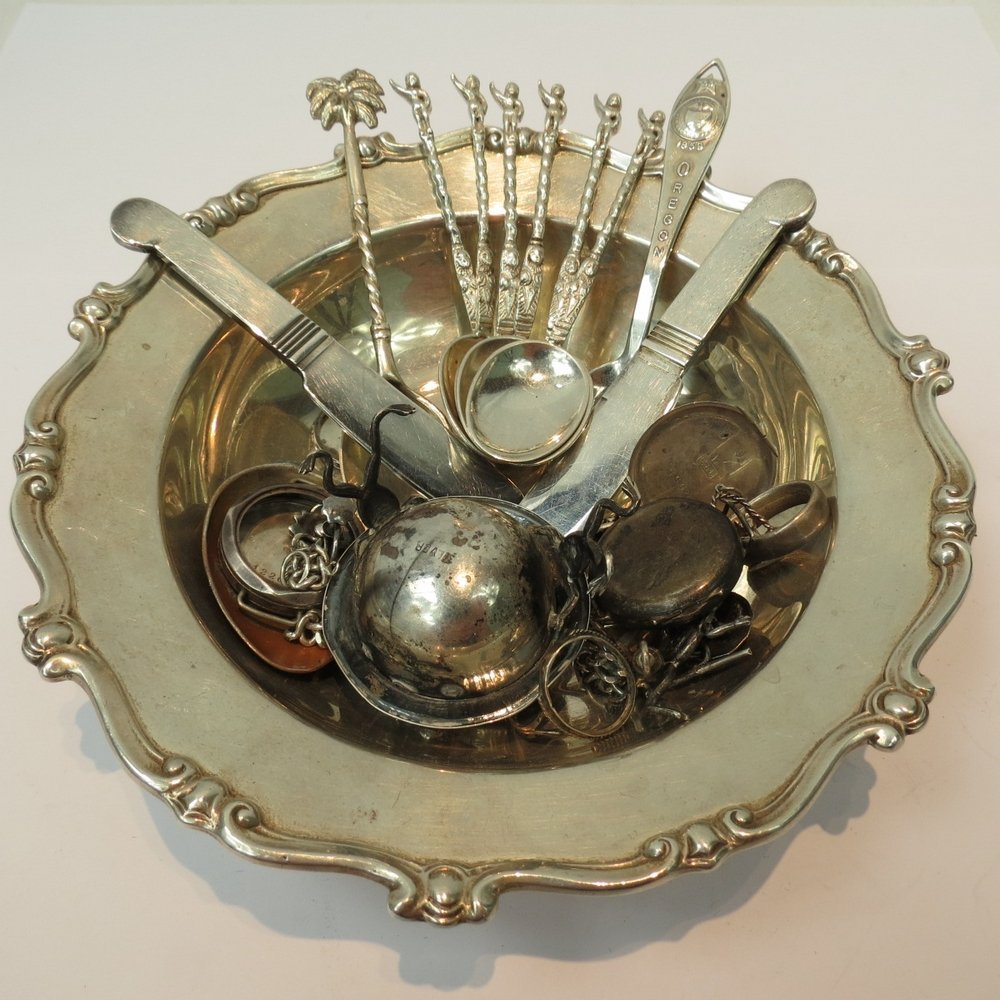 A silver circular dish with a broad scro