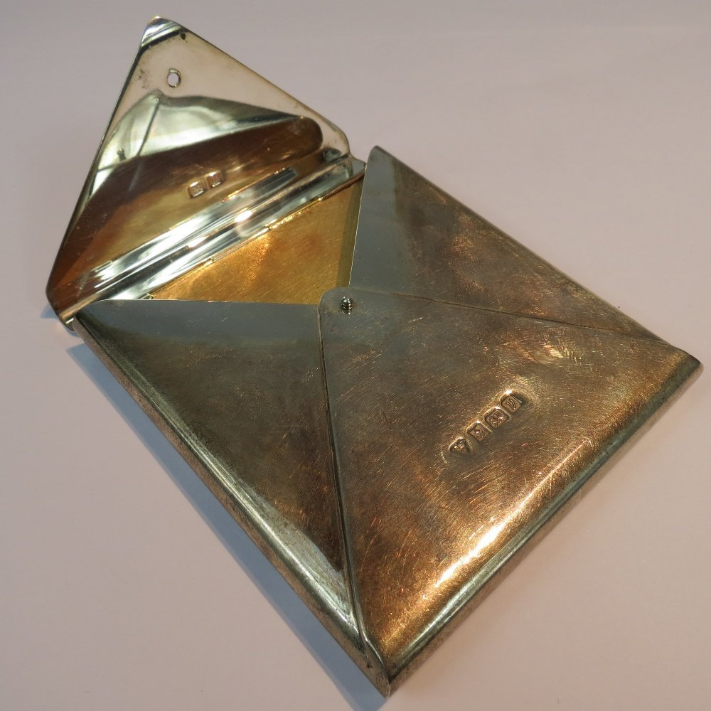 A silver cigarette case in the shape of