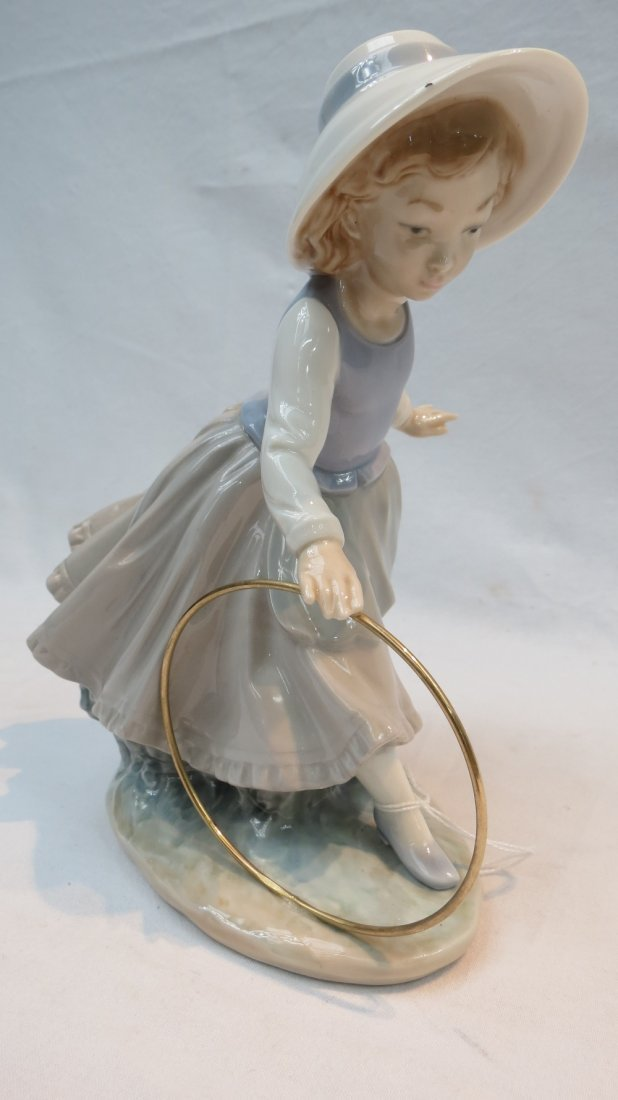 A Lladro Nao figure of a girl with a hoop, in typical