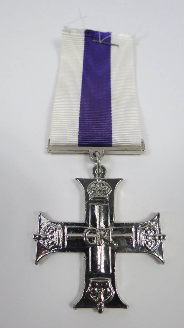 A reproduction Military Cross with ribbon.