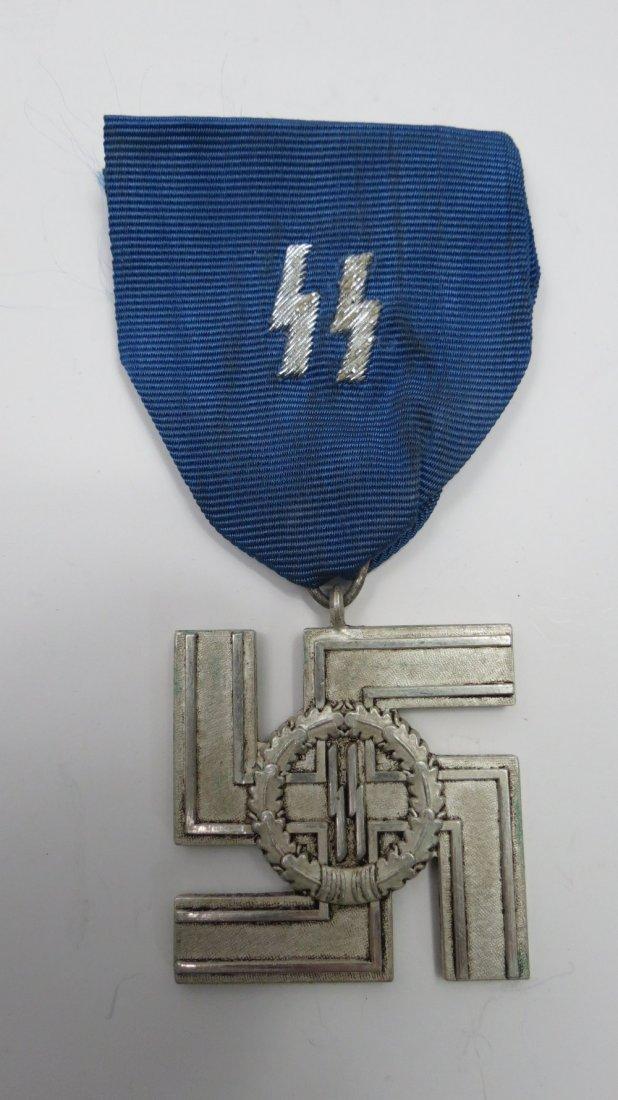 A Nazi SS medal, white metal swastika with oak leaf