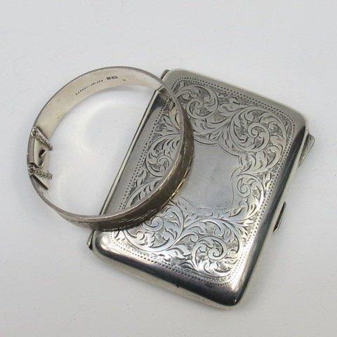 An HM silver cigarette case with foliate scroll