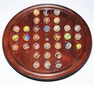 Solitaire Board of 32 Joseph Coat Swirl Marbles.