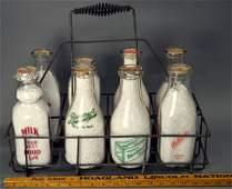 8 vintage milk bottles with caps, in metal carrier