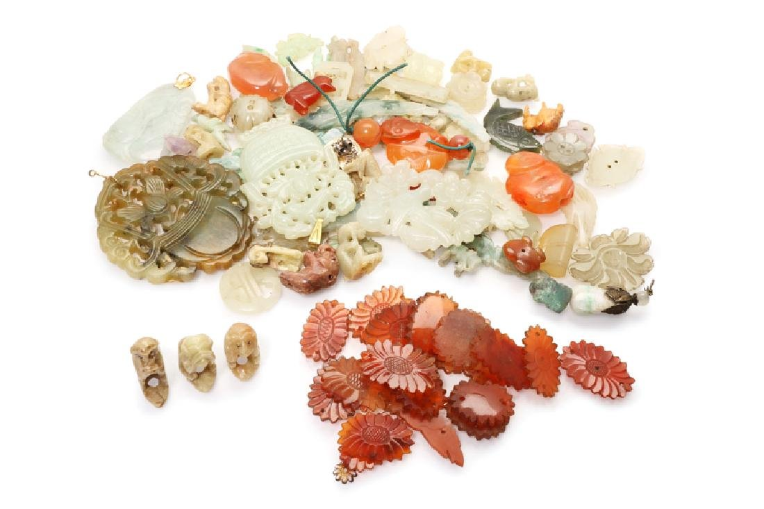 A large group of carved gemstone pendants and fragments
