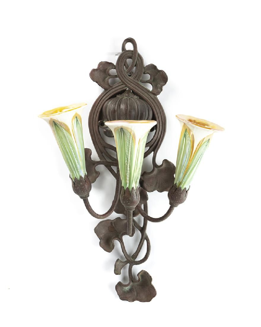 An Art Nouveau wall sconce with iridescent glass shades