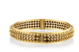 A gold cannetille hinged bangle bracelet