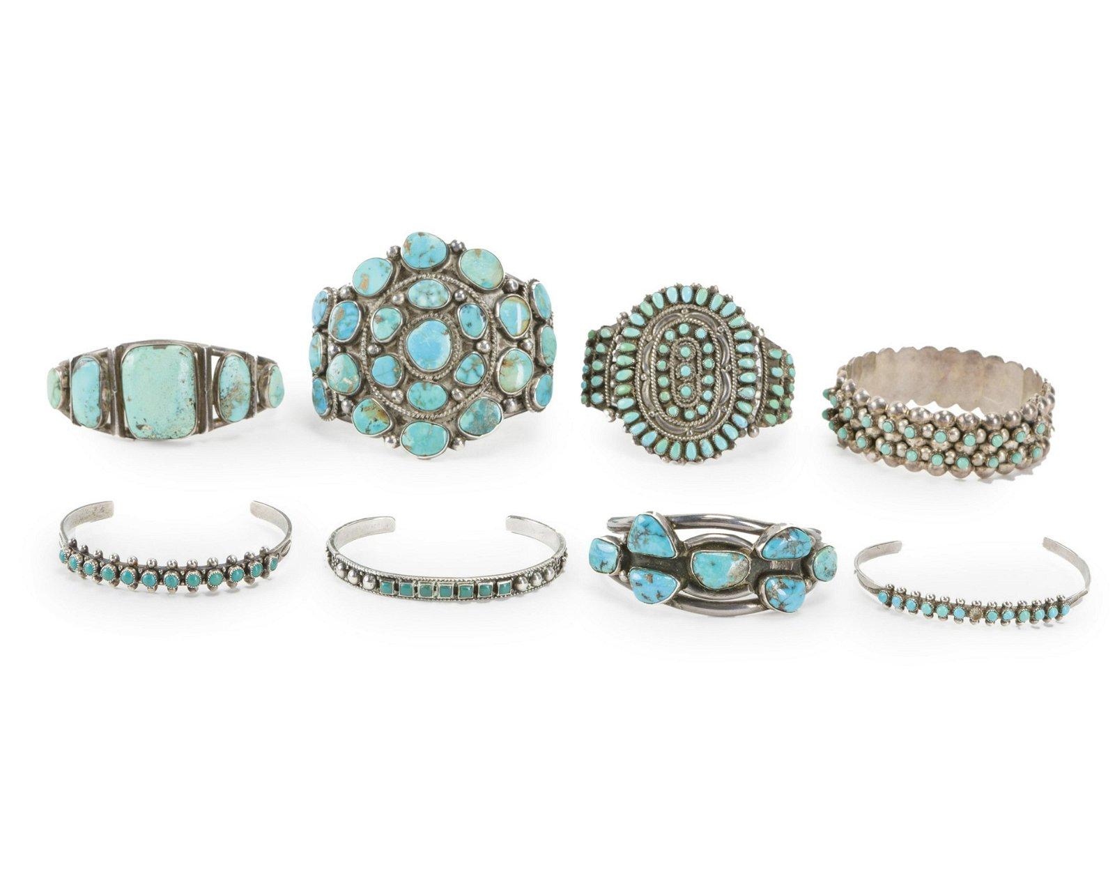 A group of silver cuff bracelets