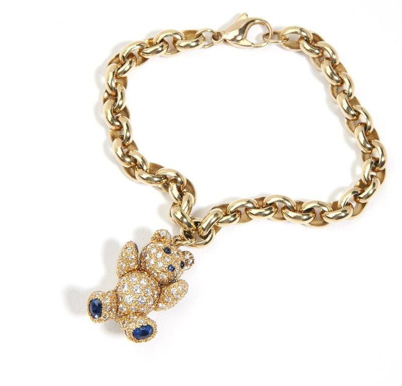 A diamond and gold teddy bear charm bracelet