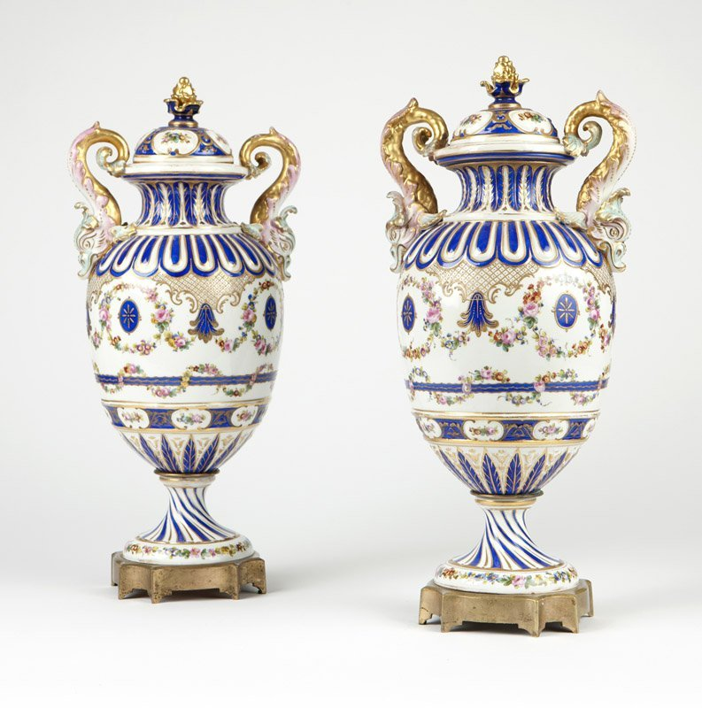 A pair of Sevres style white-ground porcelain urns