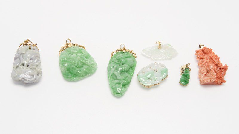 A group of carved jade and coral pendants