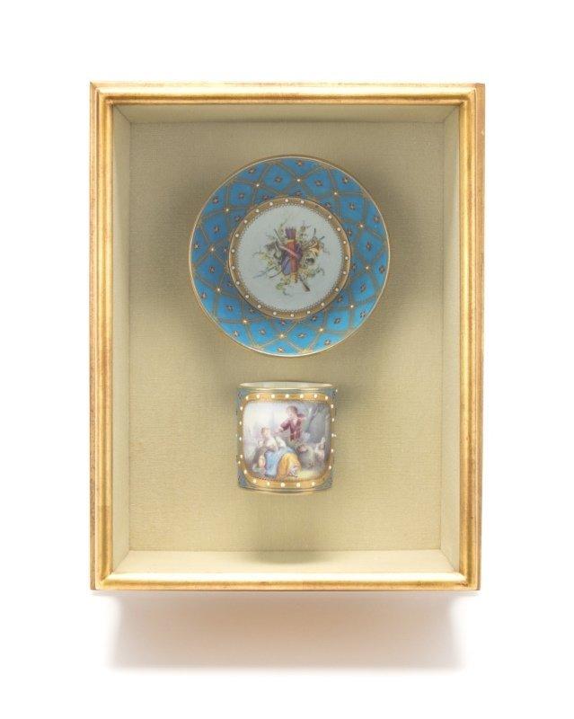 A framed Sevres-style bleu celeste cup and saucer