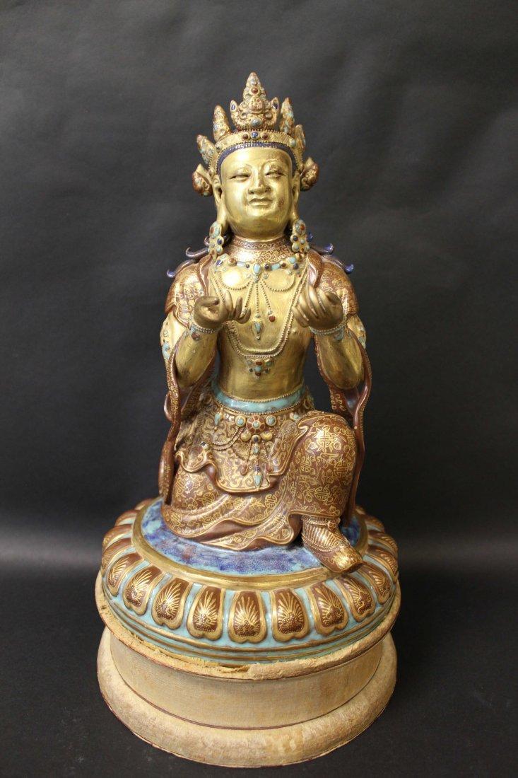 QING DYNASTY, A GUILT POCELAIN BUDDHA .