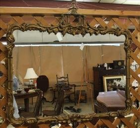Hanging wall mirror in ornate gold frame