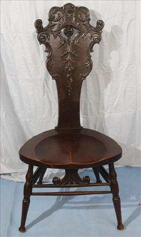 Heavily carved mahogany music chair with carving